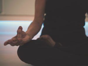Expert tips on mindfulness meditation: A woman sits in lotus position meditating