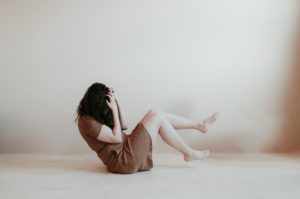 What is the best meditation for anxiety: Woman in brown dress holds her face in her hands